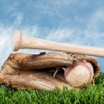 Baseball glove, ball, and bat laying on grass against a blue, lightly